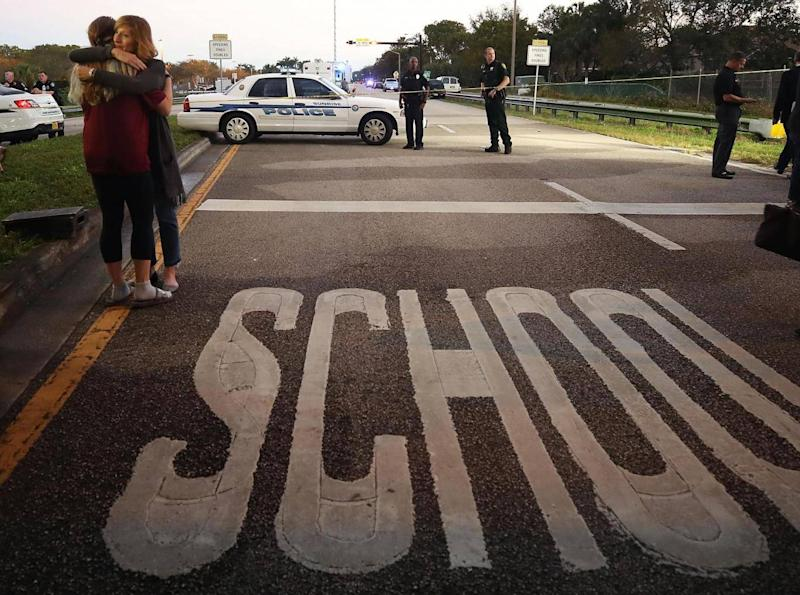 Two young women hug at a police checkpoint near the Marjory Stoneman Douglas High School where 17 people were killed by a gunman on 15 February 2018 in Parkland, Florida. (Getty)