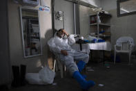 "A worker from ""Hevra Kadisha,"" Israel's official Jewish burial society, dress in full protective gear rests at a special morgue for people who died from COVID-19, during a nationwide lockdown to curb the spread of the coronavirus, in the central Israeli city of Holon, near Tel Aviv, Israel, Sunday, Jan. 10, 2021. (AP Photo/Oded Balilty)"