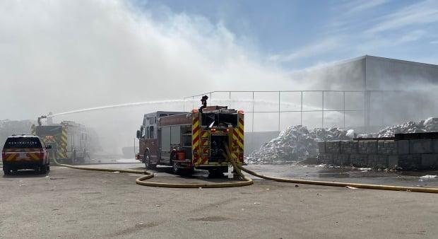 Firefighters pour water on a major fire at Crown Shred and Recycling in Regina's Eastview neigbourhood on April 8, 2021. (Trent Peppler/CBC - image credit)