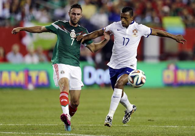 Portugal forward Nani, right, and Mexico defender Miguel Layun battle for the ball during the first half of their friendly soccer match in Foxborough, Mass., Friday, June 6, 2014. (AP Photo/Charles Krupa)