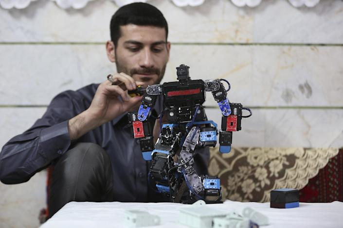 """In this picture taken on Saturday, Feb. 22, 2014, Iranian school teacher Akbar Rezaie, 27, checks his robot at his home in the city of Varamin some 21 miles (35 kilometers) south of the capital Tehran, Iran. Rezaei who has built a robot to show to children how to execute daily prayers, has innovated an amusing way of encouraging young children to say their daily prayers by using the science of robotics. Out of personal interest and unrelated to his field of study, Akbar Rezaei attended private robotics classes and acquired the skill of assembling and developing customized humanoid robots. He built the robot at home with basic tools and gave it the designation """"Veldan"""", a term mentioned in Quran meaning: """"Youth of Heaven"""". By applying some mechanical modifications such as adding up two extra engines Akbar Rezaei managed to let the robot perform praying movements, such as prostration, more easily. (AP Photo/Vahid Salemi)"""