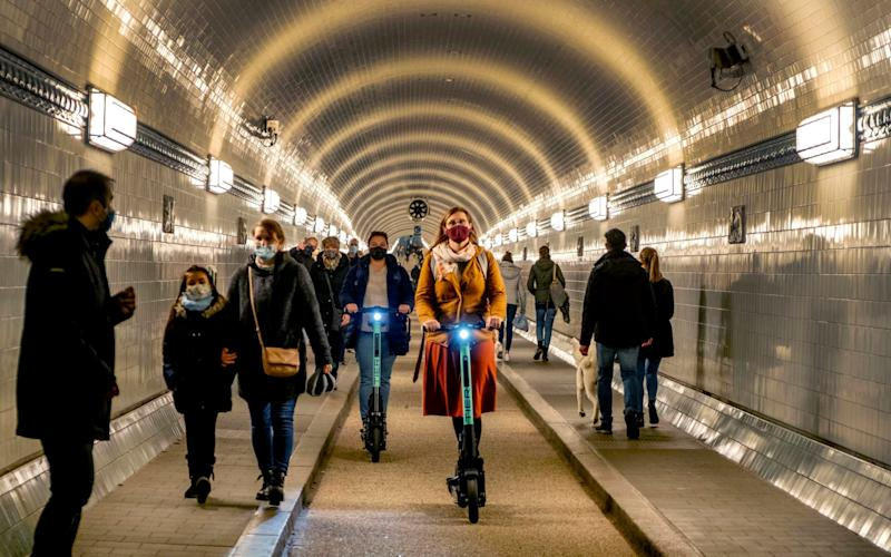 People wear face masks as they ride an E-scooter in the Old Elbe Tunnel in Hamburg, Germany, Thursday, Oct. 15, 2020. To avoid the spread of the coronavirus the use of a face mask in the 117-year-old tunnel under the Elbe river is mandatory. (AP Photo/Michael Probst) - Michael Probst/AP