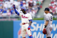 Philadelphia Phillies' Andrew McCutchen, left, reacts past New York Yankees second baseman Rougned Odor after hitting a double off pitcher Domingo German during the second inning of a baseball game, Sunday, June 13, 2021, in Philadelphia. (AP Photo/Matt Slocum)