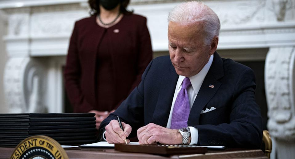 Joe Biden signs executive orders in the Oval Office on his first day of president.