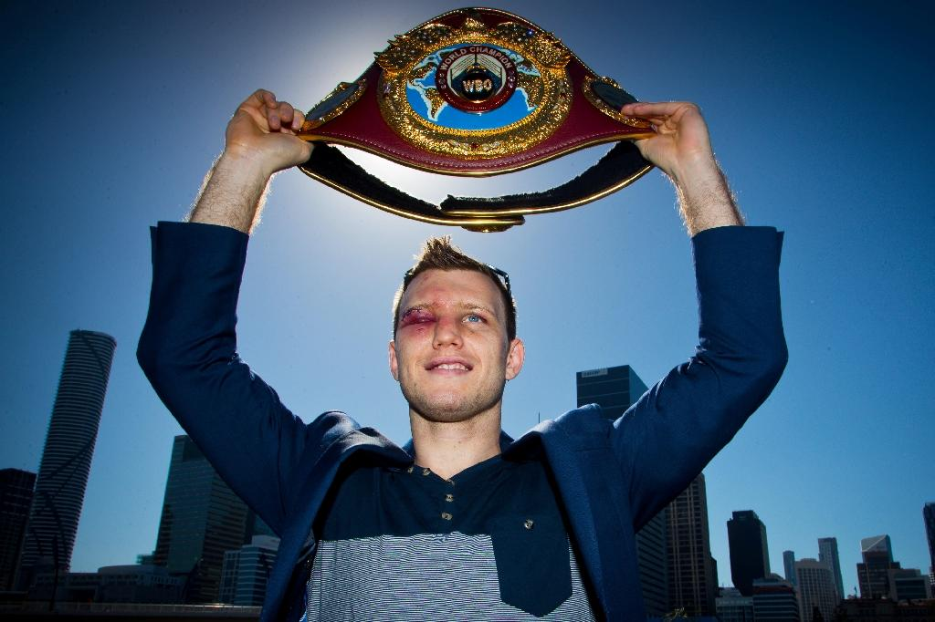 Newly crowned World Boxing Organization welterweight champion Jeff Horn of Australia poses for photographs with his belt during a press conference in Brisbane on July 3, 2017, one day after he beat the Philippines' Manny Pacquiao (AFP Photo/Patrick HAMILTON)