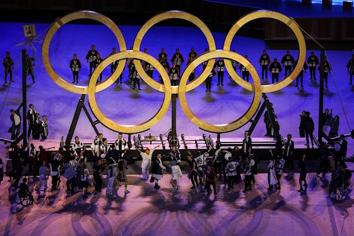 Olympic rings are assembled amid performers during the Tokyo Olympics opening ceremony.