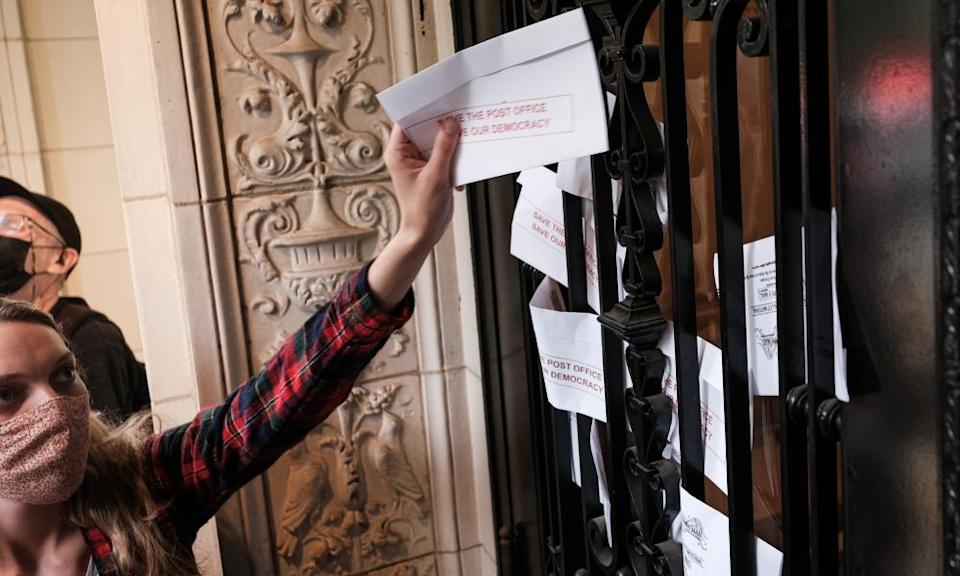 Demonstrators insert leaflets designed to look like mail-in ballots in the door of Louis DeJoy's home in Washington DC.