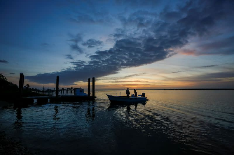 Michael Dasher, Sr., and son Michael Dasher, Jr., both of Eastpoint, Florida, U.S., leave in their boat before dawn for a day of work harvesting oysters from Apalachicola Bay