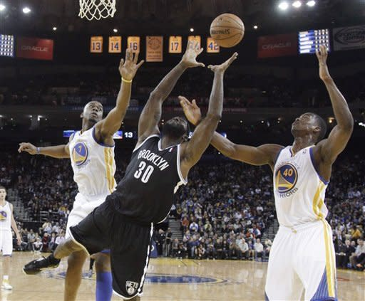 Brooklyn Nets' Reggie Evans (30) grabs a rebound between Golden State Warriors' Carl Landry (7) and Harrison Barnes (40) during the first half of an NBA basketball game in Oakland, Calif., Wednesday, Nov. 21, 2012. (AP Photo/Marcio Jose Sanchez)