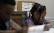"""The family rules for homeschool are posted behind Jacoby Brown, 11, and sister Felicity, 9, as they practice math at home in Austin, Texas, Tuesday, July 13, 2021. """"I didn't want my kids to become a statistic and not meet their full potential,"""" said their father, Robert, a former teacher who now does consulting. """"And we wanted them to have very solid understanding of their faith."""" (AP Photo/Eric Gay)"""