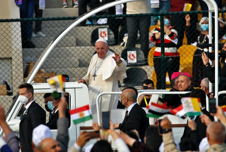 Pope Francis waves as he arrives for an open air Mass at a stadium in Irbil, Iraq, Sunday, March 7, 2021. Thousands of people filled the sports stadium in the northern city of Irbil for Pope Francis' final event in his visit to Iraq: an open-air Mass featuring a statue of the Virgin Mary that was restored after Islamic militants chopped of the head and hands. (AP Photo/Hadi Mizban)