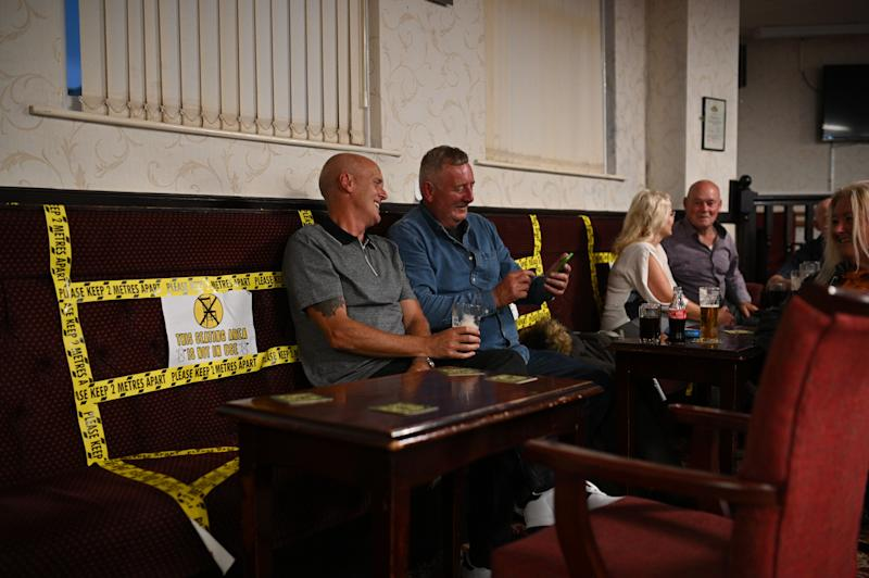 People enjoy a drink with yellow tape on the seats aiding social distancing inside the Burnley Miners Working Men's Social Club in Burnley, northwest England, on July 4, 2020, as restrictions are further eased during the novel coronavirus COVID-19 pandemic. - Pubs in England reopen on Saturday for the first time since late March, bringing cheer to drinkers and the industry but fears of public disorder and fresh coronavirus cases. (Photo by Oli SCARFF / AFP) (Photo by OLI SCARFF/AFP via Getty Images)