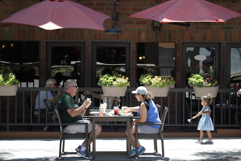 FILE - In this July 18, 2020 file photo, patrons eat at a table set up on a sidewalk in Burbank, Calif. California's financially battered restaurants filed government claims Monday to recover more than $100 million in fees for liquor and health permits and tourism charges that they say were assessed even though their businesses were shuttered or only partially operating under long-running coronavirus orders. Few industries have been hit as hard during the pandemic as restaurants. (AP Photo/Marcio Jose Sanchez, File)