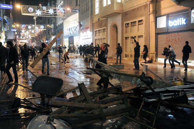 Protesters clash with riot police at a barricade in Istanbul, Turkey, Friday, Dec. 27, 2013. Turkish Prime Minister Recep Erdogan on Friday faced mounting accusations of trying to cover up a corruption scandal that has implicated his allies after a prosecutor said he was being prevented from expanding a corruption probe. Erdogan was forced to reshuffle his government this week after three ministers, whose sons were detained as part of the probe, resigned. (AP Photo / Emrah Gurel)