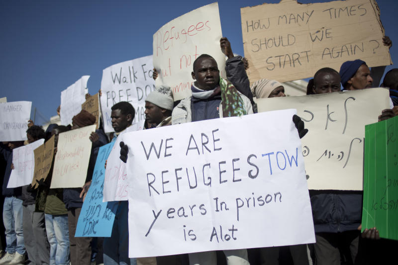 African migrants hold signs during a protest in Jerusalem, Tuesday, Dec. 17, 2013. Chanting slogans and calling for freedom, some 200 African migrants and Israeli activists ended a two-day march with a rally on Tuesday denouncing Israel's policy of detaining those illegally in the country. (AP Photo/Ariel Schalit)