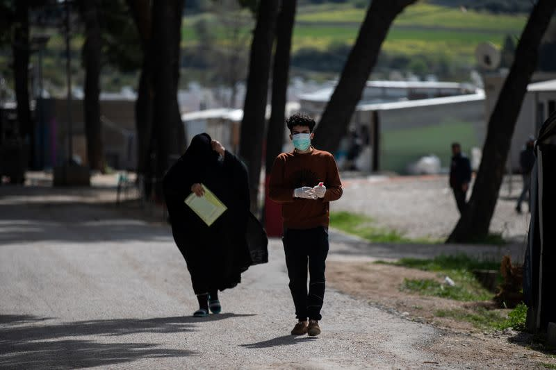 A migrant wearing a protective face mask makes his way in the Ritsona camp, after authorities found 20 coronavirus cases and placed the camp under quarantine, following the outbreak of coronavirus disease (COVID-19)