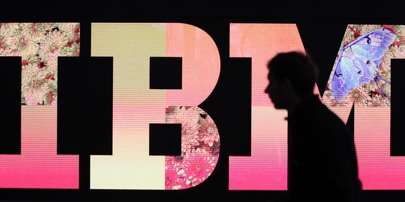 A man passes by an illuminated IBM logo at the CeBIT computer fair in Hanover