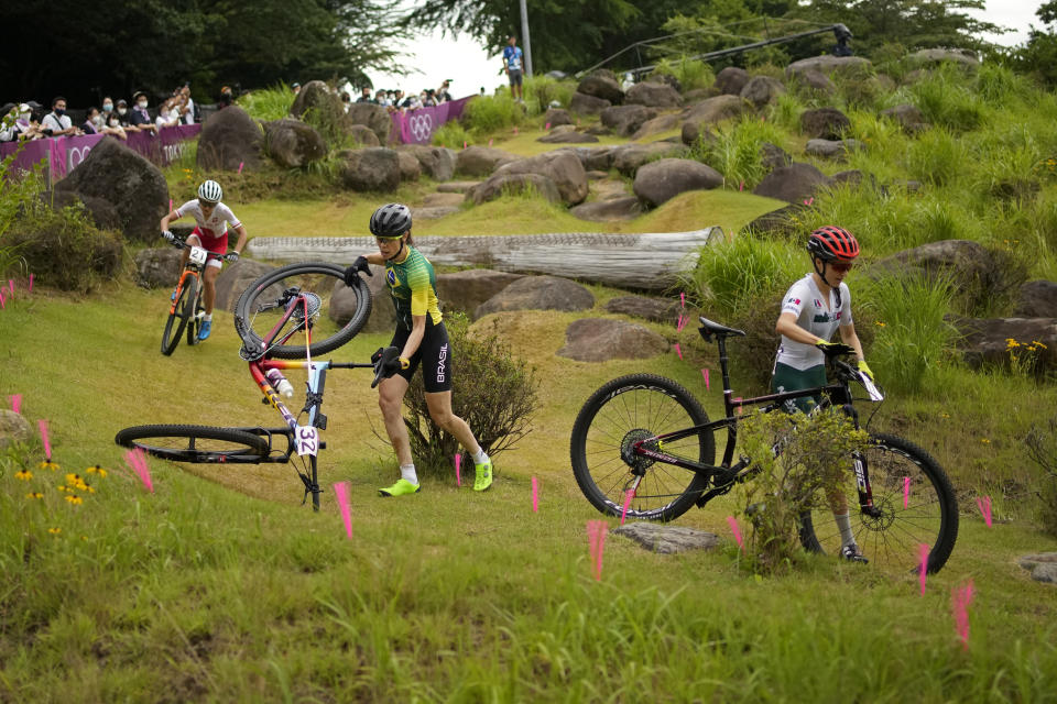 Jaqueline Mourao of Brazil picks up her bike after falling as she competes with Daniela Campuzano Chavez Peon of Mexico, right, andMaja Wloszczowska of Poland (21) during the women's cross-country mountain bike competition at the 2020 Summer Olympics, Tuesday, July 27, 2021, in Izu, Japan. (AP Photo/Christophe Ena)