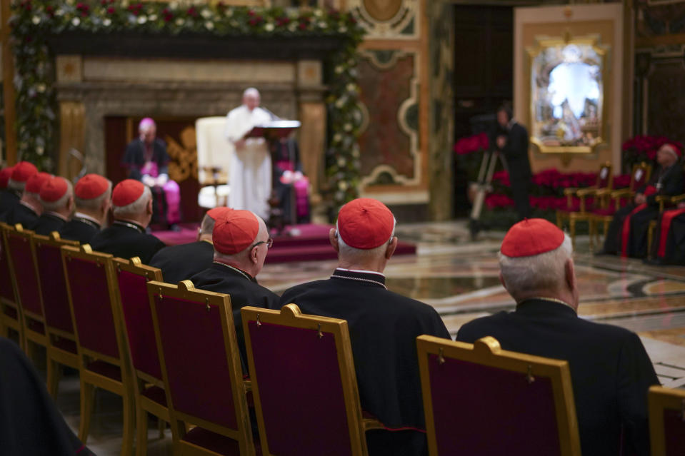 "FILE - Cardinals listen as Pope Francis, background, delivers his Christmas greetings to the Roman Curia, in the Clementine Hall at the Vatican, Saturday, Dec. 21, 2019. Pope Francis has ordered pay cuts for Holy See employees, including slashing cardinals' salaries by 10%. Francis in a letter made public by the Vatican on Wednesday, March 24, 2021, noted that the pandemic emergency ""negatively impacted all sources of revenue"" for the Holy See and Vatican City State. (AP Photo/Andrew Medichini, File)"