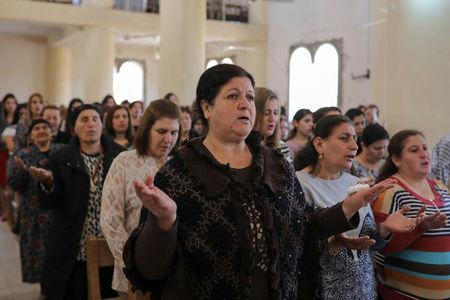 Believers take part in the Easter Mass in Mar Gewargis (St George) Chaldean Catholic church, which was damaged by Islamic State militants, in the town of Tel Esqof