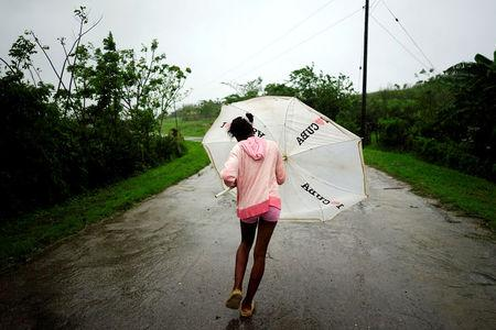 Dalma Samora, 14, walks against the winds of Subtropical Storm Alberto as it passes by the west coast of Cuba, in La Palma, Cuba, May 26, 2018.  REUTERS/Alexandre Meneghini