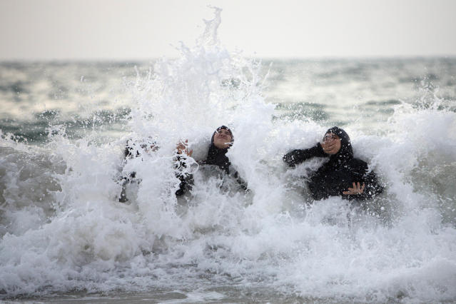 <p>Palestinian women enjoy the Mediterranean sea during the Eid al-Fitr holiday in Tel Aviv, Israel, Aug. 10, 2013. (Photo: Oded Balilty/AP) </p>