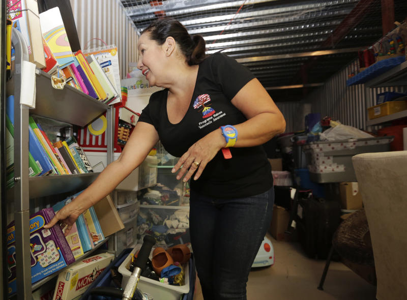 """In this April 11, 2017 photo, Mariela Reyes, a volunteer with Venezuelan Roots, sorts through donated goods for newly arrived Venezuelan immigrants at the """"Value Store It"""" in Doral, Fla. Many of the Venezuelans now seeking food and other assistance in South Florida were once professionals or members of the middle class in their homeland, people who decided they could no longer tolerate increasing misery, crime, food shortages and lack of medical care. (AP Photo/Lynne Sladky)"""