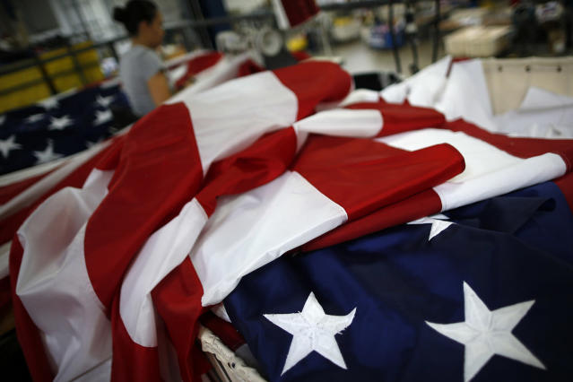 <p>American flags sit as a worker sews at the FlagSource facility in Batavia, Illinois, U.S., on Tuesday, June 27, 2017. (Photo: Jim Young/Bloomberg via Getty Images) </p>