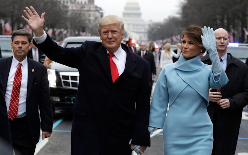 US President Donald J. Trump (C-L) waves as he walks with First Lady Melania Trump (C-R) during the the Inaugural Parade after Trump was sworn in as the 45th President of the United States in Washington, DC, USA, 20 January 2017. - Credit: EVAN VUCCI/POOL/EPA