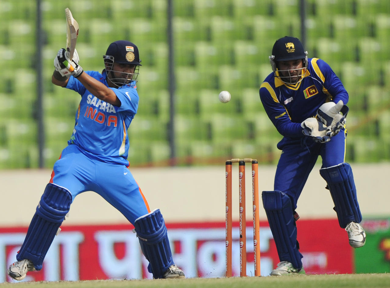 Indian batsman Gautam Gambhir (L) plays a shot as Sri Lankan wicketkeeper Kumar Sangakkara (R) reacts during the one day international (ODI) Asia Cup cricket match between India and Sri Lanka at The Sher-e-Bangla National Cricket Stadium in Dhaka on March 13, 2012. AFP PHOTO/Munir uz ZAMAN (Photo credit should read MUNIR UZ ZAMAN/AFP/Getty Images)