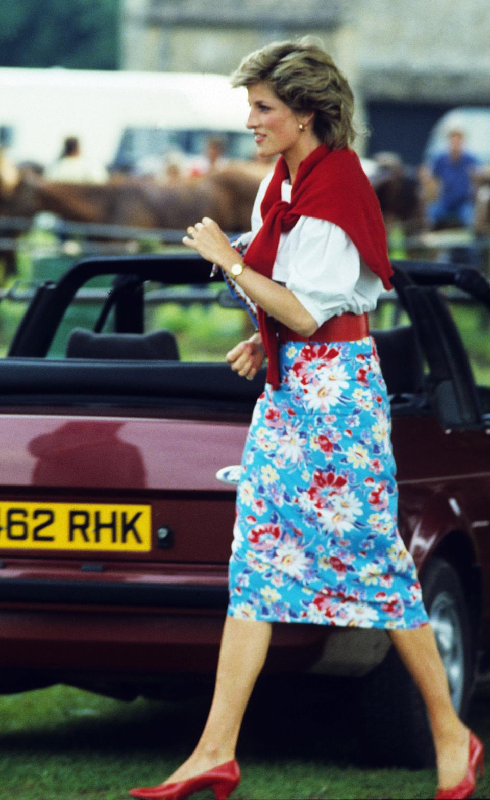CIRENCESTER, ENGLAND - JUNE 30: Diana, Princess of Wales, wearing a blue floral patterned pencil skirt with a red belt, white blouse and red cardigan worn around her shoulders, attends a polo match at Cirencester Park Polo Club on June 30, 1985 in Cirencester, United Kingdom. (Photo by Anwar Hussein/WireImage)