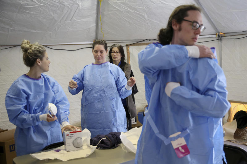 Philadelphia Medical Reserve Corps volunteers, from left, Marina Spitkovskaya, Megan Boyle, and Stephen Bonett , all of whom are nurses, put on their protective outfits with the help of Dr. Felicia Lewis, a Philadelphia Department of Public Health medical epidemiologist, as the city's coronavirus testing site prepared to open next to Citizens Bank Park in South Philadelphia on Friday, March 20, 2020. The site, which opened Friday afternoon, is the first city-run location where people can be swabbed to determine if they have the coronavirus. At the time of opening, it was only for people with symptoms who are over 50 and healthcare workers with symptoms.(Tim Tai/The Philadelphia Inquirer via AP)
