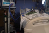 A COVID-19 patient, placed on a ventilator, rests at St. Joseph Hospital in Orange, Calif. Thursday, Jan. 7, 2021. California health authorities reported Thursday a record two-day total of 1,042 coronavirus deaths as many hospitals strain under unprecedented caseloads. (AP Photo/Jae C. Hong)