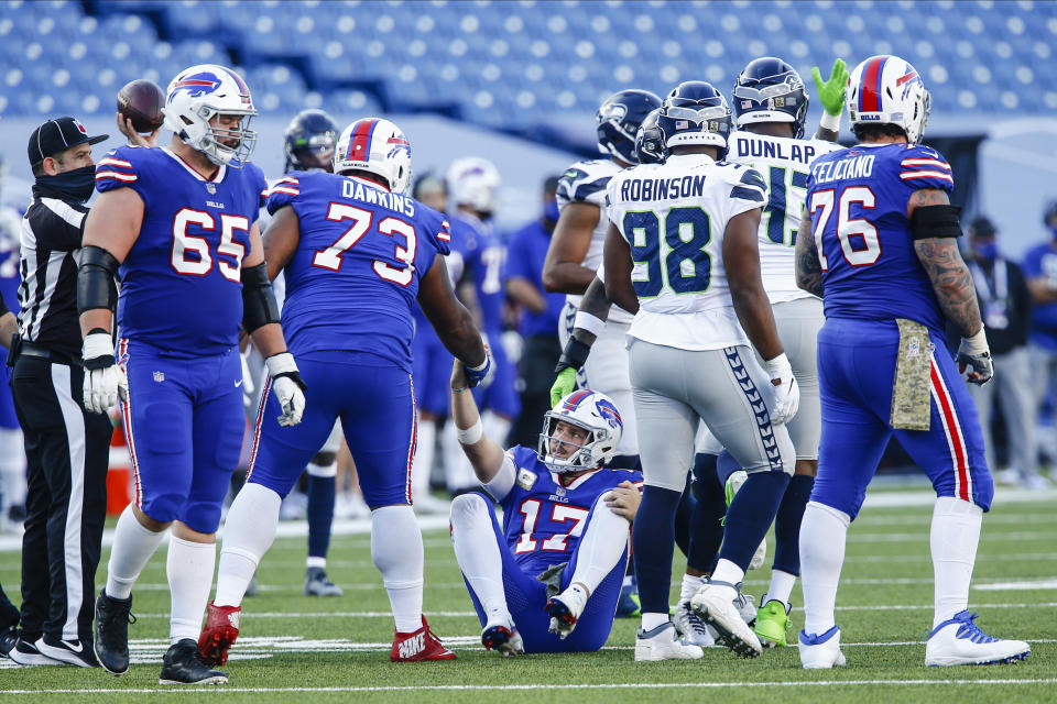 Buffalo Bills quarterback Josh Allen (17) is helped up by a teammate after being sacked by Seattle Seahawks' Carlos Dunlap during the second half of an NFL football game Sunday, Nov. 8, 2020, in Orchard Park, N.Y. (AP Photo/John Munson)