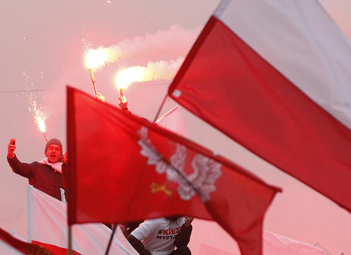 Members of right-wing groups light up flares during a march by some tens of thousands of people and hosted by President Andrzej Duda that marked 100-years since Poland regained independence, in Warsaw, Poland, Sunday, Nov. 11, 2018. (AP Photo/Czarek Sokolowski)