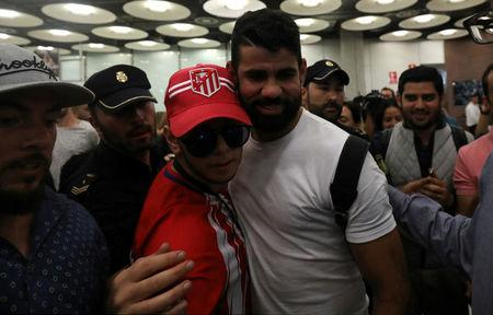 Spain's soccer player Diego Costa poses with an Atletico Madrid's supporter upon arriving at Adolfo Suarez Madrid Barajas airport in Madrid, Spain, September 22, 2017. REUTERS/Sergio Perez