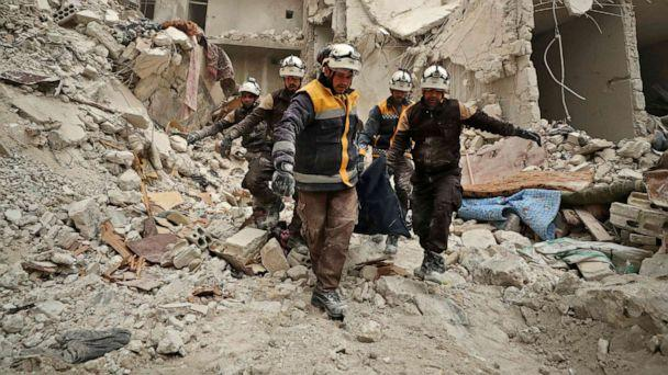 PHOTO: Rescue workers known as the White Helmets carry away the body of a victim found amidst the rubble of a building, hit during an air strike by pro-regime forces on the rebel-held town of Ariha, Idlib province, Syria, Feb. 5, 2020. (Omar Haj Kadour/AFP via Getty Images)