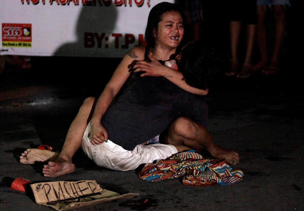 "ATTENTION EDITORS - VISUAL COVERAGE OF SCENES OF INJURY OR DEATHA woman cradles the body of her husband, who was killed on a street by a vigilante group, according to police, in a spate of drug related killings in Pasay city, Metro Manila, Philippines July 23, 2016. A sign on a cardboard found near the body reads: ""Pusher Ako"", which translates to ""I am a drug pusher.""  REUTERS/Czar Dancel"