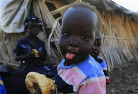 South Sudanese refugee children eat near a border gate in Joda, in the Jableen locality in Sudan's White Nile State