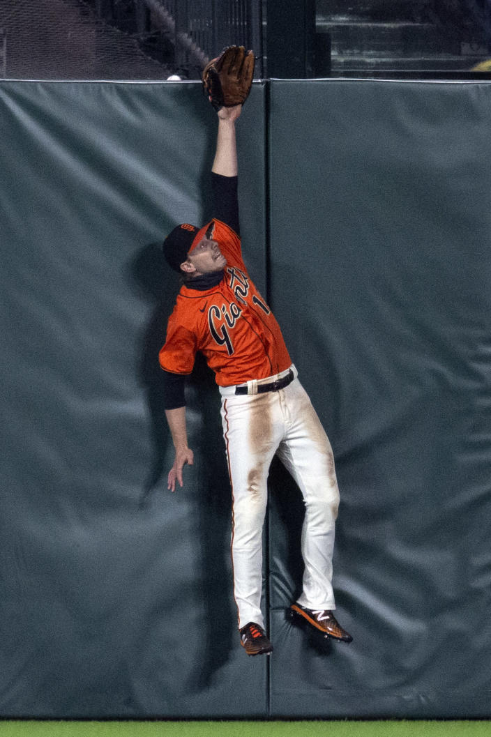 San Francisco Giants center fielder Austin Slater leaps in vain for a two-run home run by San Diego Padres' Trent Grisham's during the sixth inning of a baseball game Friday, May 7, 2021, in San Francisco. (AP Photo/D. Ross Cameron)