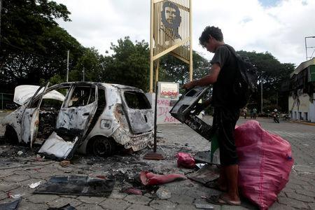 A man stands next to a burned car after a protest against Nicaraguan President Daniel Ortega's government in Managua, Nicaragua May 31, 2018.REUTERS/Oswaldo Rivas