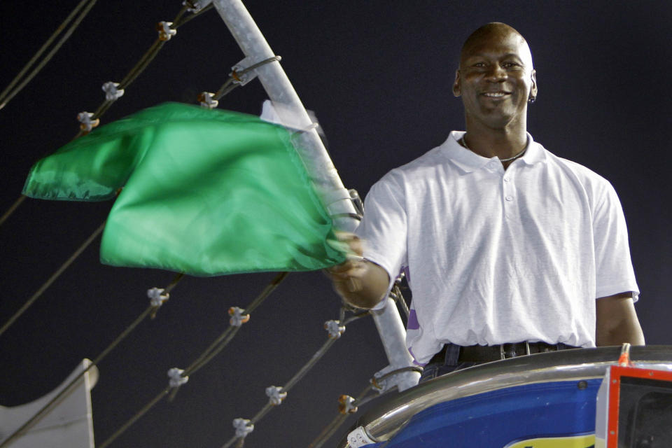 FILE - In this May 22, 2010, file photo, Charlotte Bobcats owner Michael Jordan practices waving the green flag before a NASCAR All-Star auto race at Charlotte Motor Speedway in Concord, N.C. NASCAR needs to roll out the red carpet when the Daytona 500 opens the season Sunday. Michael Jordan and the rapper Pitbull, racing's newest team owners, are expected to attend.  (AP Photo/Chuck Burton, File)