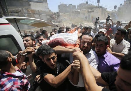 Palestinians carry the body of Mohammed Abu Shammala, one of three senior Hamas commanders who was killed in an Israeli air strike, during his funeral in Rafah in the southern Gaza Strip August 21, 2014.  REUTERS/Ibraheem Abu Mustafa