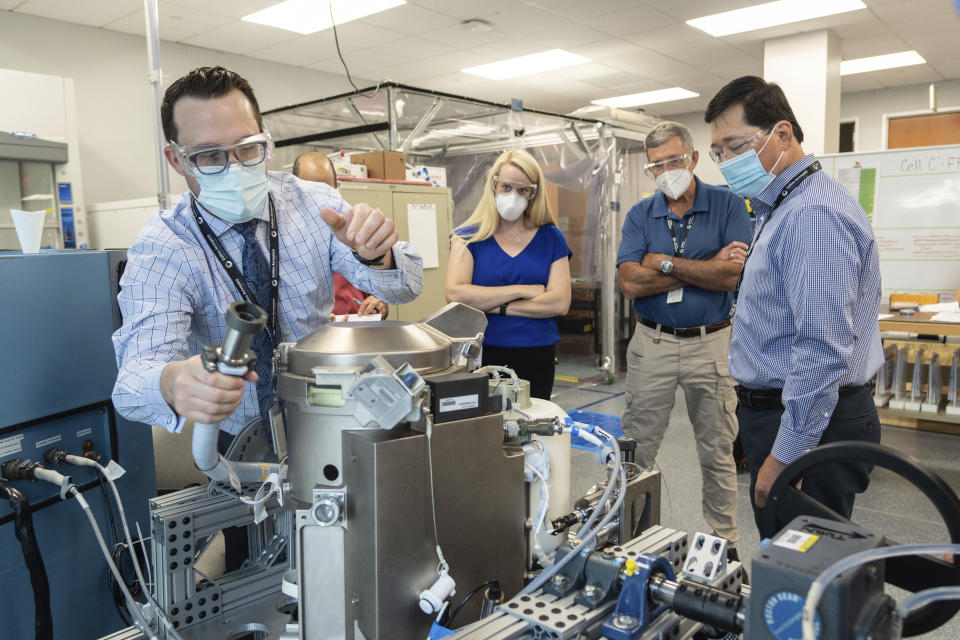 In this June 18, 2020 photo provided by NASA, astronaut Kate Rubins, center, and support personnel review the Universal Waste Management System, a low-gravity space toilet, in Houston. The new device is scheduled to be delivered to the International Space Station on Oct. 1, 2020. (Norah Moran/NASA via AP)