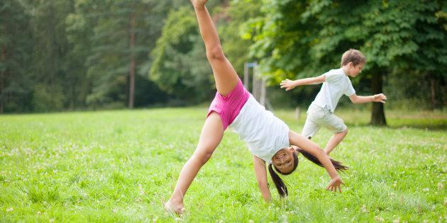 A child does a cartwheel in a field.