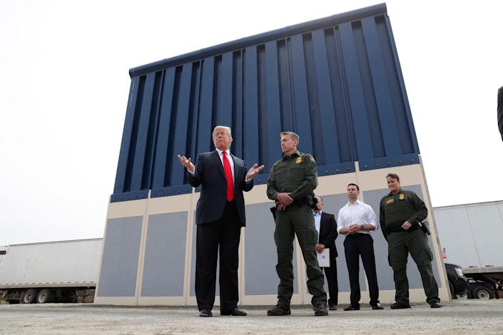 President Donald Trump stands with a Customs and Border Protection agent in front of a border wall prototype while visiting San Diego last month. (Photo: Kevin Lamarque / Reuters)