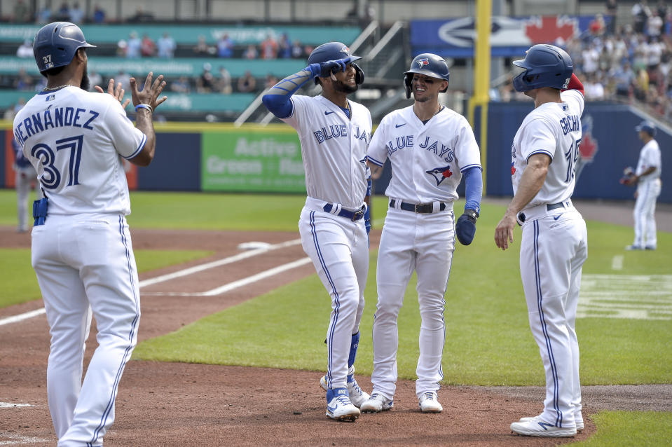 Toronto Blue Jays' Lourdes Gurriel Jr., third from right, celebrates his grand slam with Teoscar Hernandez, left, Cavan Biggio, second from left, and Randal Grichuk, right, during the first inning of the second baseball game of a doubleheader against the Texas Rangers in Buffalo, N.Y., Sunday, July 18, 2021. (AP Photo/Adrian Kraus)