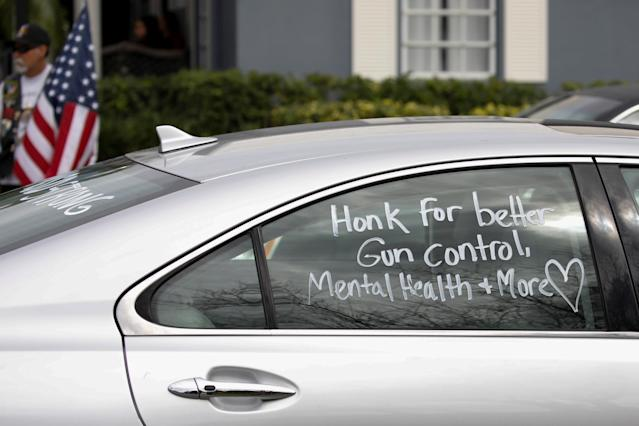 <p>A car with a message in support of gun control written on the window drives past the funeral service for Marjory Stoneman Douglas High School student Peter Wang in Coral Springs, Fla., Feb. 20, 2018. (Photo: Carlos Garcia Rawlins/Reuters) </p>