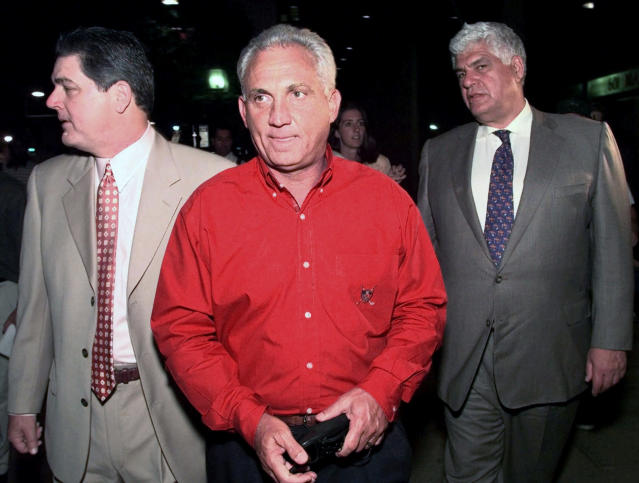 FILE - In this Sept. 1, 1999, file photo, National League umpire Richie Garcia, center, walks with umpire and union president Jerry Crawford, left, and union chief Richie Phillips as they leave Federal Court in Philadelphia. Ten years after Garcia was fired by Major League Baseball, he wants to set the record straight: He did not get fired for trying to evaluate his son-in-law, then a minor league umpire. Garcia thinks baseball's top executives just wanted him out. (AP Photo/Chris Gardner, File)