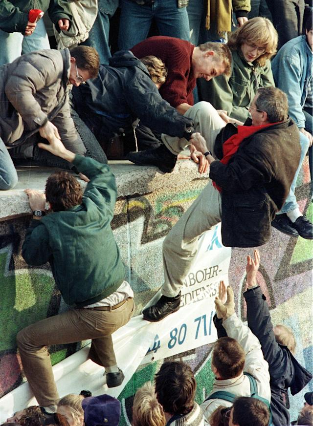 East German citizens help each other climb the Berlin Wall at the Brandenburg Gate on Nov. 10, 1989. (Photo: Reuters)
